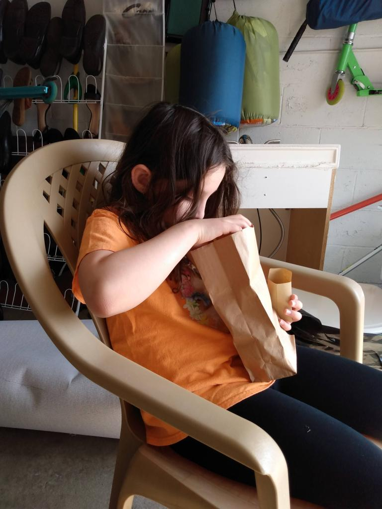 Image of 8 year old girl stuffing a small envelope with seeds from a brown paper bag.